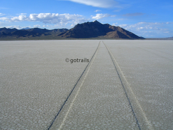 Scene of a long car trace on plain salty sands toward mountains and cloudy sky